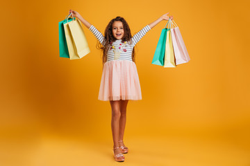 Cheerful girl child holding shopping bags. Wall mural