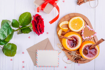 Festive composition with greeting card, fresh flower, gift and unusual served in orange mulled wine on the white wooden table. Valentine' s day surprize for lover. Selective focus, copy space.