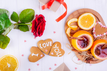 Festive composition with cookies in shape of heart with I Love you words, rose, unusual served in orange mulled wine on the white table. Valentine' s day surprize for lover. Selective focus.