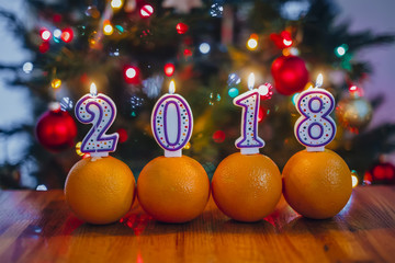 Oranges and lighted candles on a table in the background of lights. the concept of Happy New Year 2018