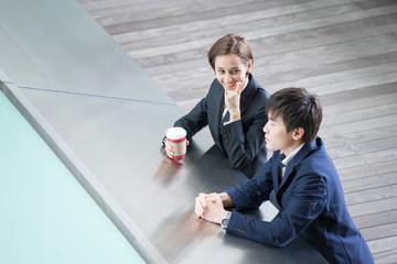 屋外でコーヒーを飲みながら会話する男女