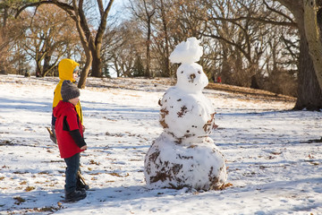 children and snowman in the park in the spring. melted snowman. The concept of springtime. Copy space for your text