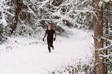Young man running in the snow in Austria