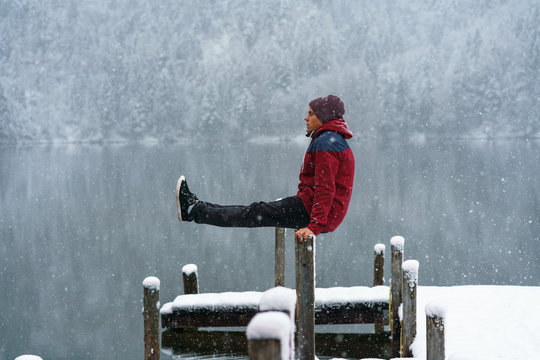 Young man doing a workout at a lake in Austria in winter