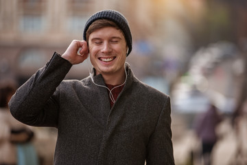 Enjoy the sound. Waist up portrait of joyful man walking in the city while enjoying favorite songs