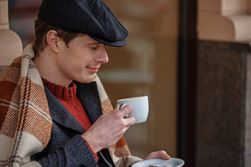 Young male enjoying coffee aroma while sitting at cafe with blanket. Copy space in right side