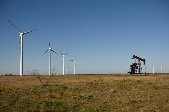 Wind energy turbines and crude oil pump jack pumping oil in West Texas, USA