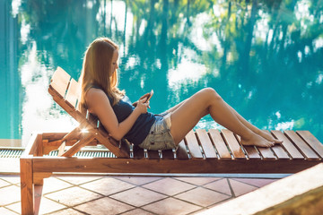 Happy smartphone woman relaxing near swimming pool. Beautiful girl using her mobile phone app 4g data to play songs while relaxing on summer luxury vacations