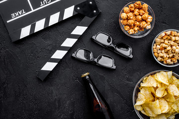 Crisp, popcorn, rusks for watching film. Clapperboard and glasses on black background top view copyspace