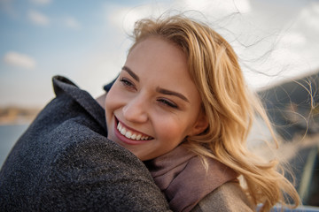 Long-awaited meeting. Close up portrait of young woman in arms of boyfriend while smiling and standing