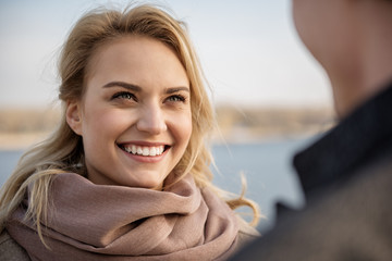 Close up of young lady emotionally smiling to man while dating. Focus on girl while they are standing in open air