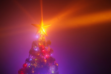 Christmas tree with festive lights, purple background with mist