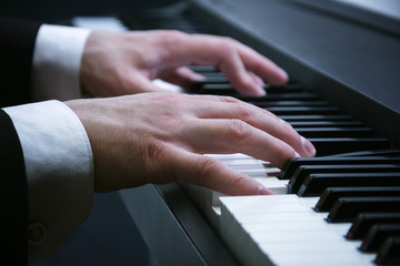 man's hands playing on a piano at the concert
