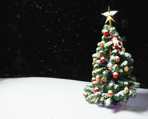Christmas tree with festive lights in snow outdoors, black night background