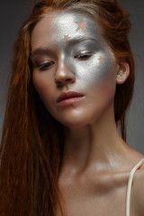 A young girl with red hair and a brilliant silver make-up with the stars. Beautiful model with shining skin. Holiday image. Beauty of the face. Photo taken in the studio.