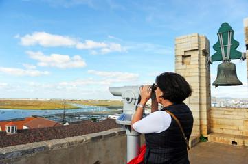Mujer observando una panorámica de la ría de Faro desde la torre campanario de la catedral de Santa María, Algarve, sur de Portugal