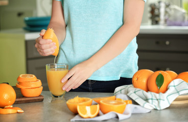 Woman squeezing orange juice into glass in kitchen