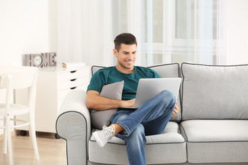 Handsome man using laptop while resting on sofa at home