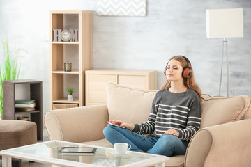 Beautiful woman listening to music while resting on sofa at home