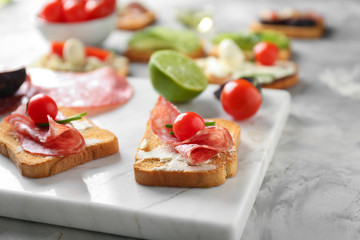 Delicious sandwiches with salami and cherry tomatoes on board, closeup