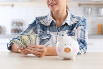 Woman with piggy bank and money at table, closeup