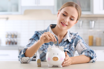 Young woman putting coin into piggy bank at table indoors