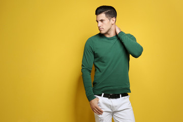 Handsome young man in casual clothes on color background Wall mural