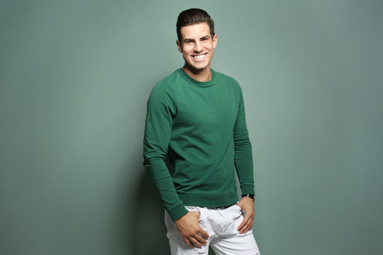 Handsome young man in casual clothes on color background