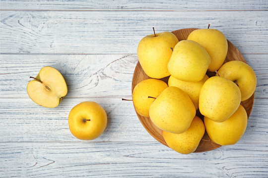 Ripe yellow apples on wooden background, top view