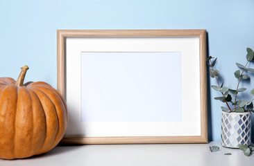 Mockup of blank frame with pumpkin on color background