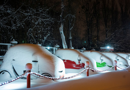 Smart cars covered in snow after a heavy snowfall are parked in a line for sale outside an automobile dealership in Kiev