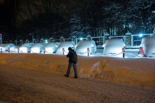 A man passes by smart cars covered in snow parked in a line for sale outside an automobile dealership, after a heavy snowfall, in Kiev