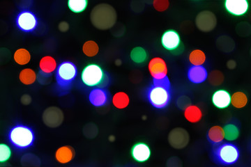 Celebration atmosphere. Bokeh of multicolored highlights on a black background.