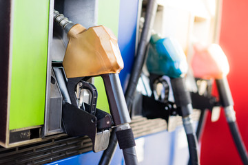 Colorful Petrol pump filling nozzles.Gas station in a service in warm sunset.