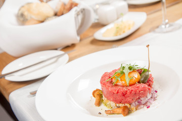 Steak tartare served in a restaurant with egg yolk,  onions, caper, mushroom and rocket salad