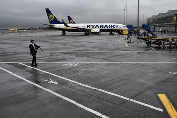A man walks past a Ryanair aeroplane at Stansted airport in London
