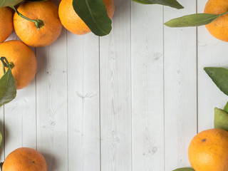 Fresh mandarin or tangerines with stems and leaves on white wooden background Copy space