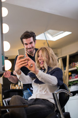 Hairdresser and his client making selfie