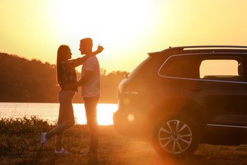 Beautiful young couple standing near car