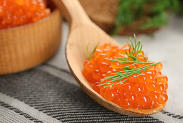 Wooden spoon with delicious red caviar on table, closeup