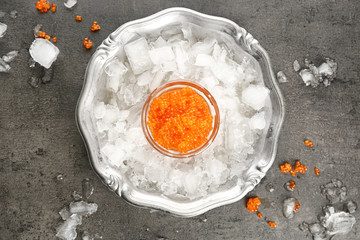 Bowl with delicious red caviar and ice on metal tray