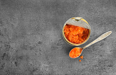 Delicious red caviar in tin can and spoon on grey background