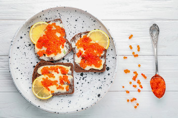 Tin can with delicious red caviar, dill and sandwich on table