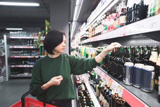 A young girl chooses beer in a supermarket. A beautiful girl buys an alcohol in the store. Shopping in a supermarket.