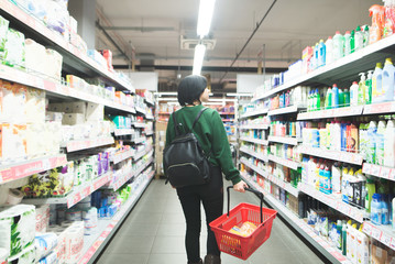 A young girl walks through the supermarket and makes a purchase. Backpacker's girlfriend who goes shopping and buys goods.
