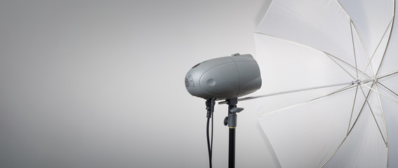 Photography set up. Professional photography studio flash light with reflective umbrella.