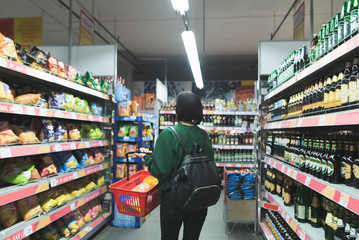 The girl goes to the supermarket and chooses goods. The buyer buys the products in the store.