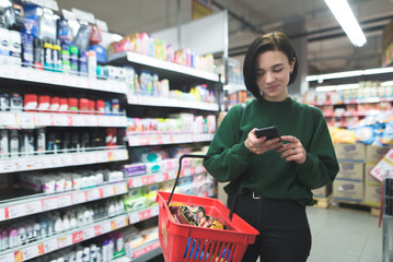 A positive girl uses a phone in a supermarket. A girl shopping in a supermarket with a phone in her hands. Focus on your phone