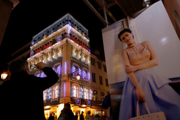 A man takes a picture of a building decorated with Christmas lights in downtown Lisbon