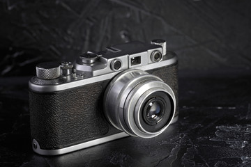 Old rangefinder film camera on a black concrete background.